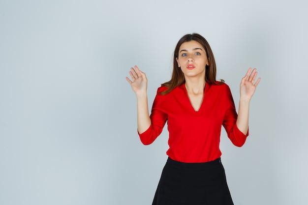 Молодая женщина показывает ладони в жесте капитуляции в красной блузке, юбке и выглядит испуганной