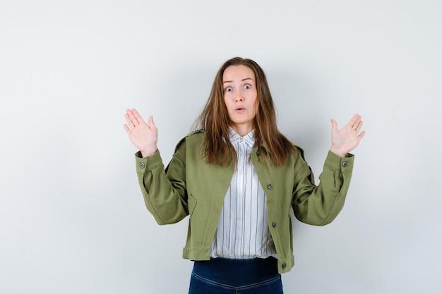 Молодая леди показывает ладони в жесте капитуляции в рубашке, куртке и выглядит испуганной, вид спереди.