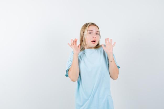 Tシャツで降伏ジェスチャーで手のひらを示し、困惑しているように見える若い女性。正面図。