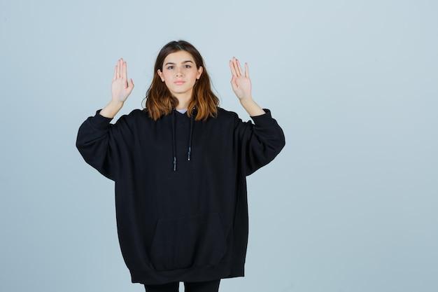 Giovane donna che mostra le palme in felpa con cappuccio oversize, pantaloni e sembra sicura di sé, vista frontale.