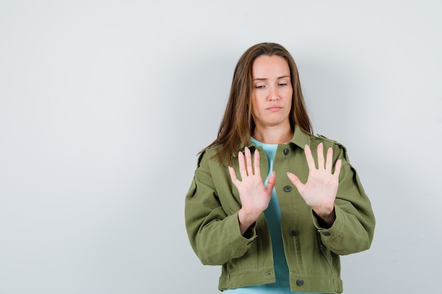 Young lady showing palms in t-shirt, jacket and looking serious. front view.