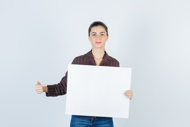 Young lady showing paper poster in shirt, jeans front view.