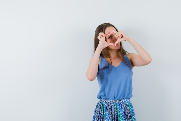Молодая дама показывает жест мира над глазом в блузке, юбке и выглядит милой. передний план. место для текста