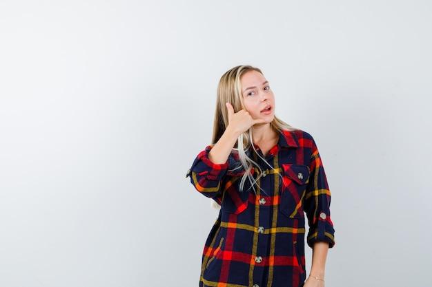 Молодая леди показывает жест телефона в проверенной рубашке и выглядит уверенно, вид спереди.