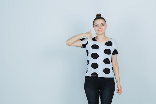 Молодая леди показывает жест телефона в футболке, джинсах и выглядит счастливым, вид спереди.