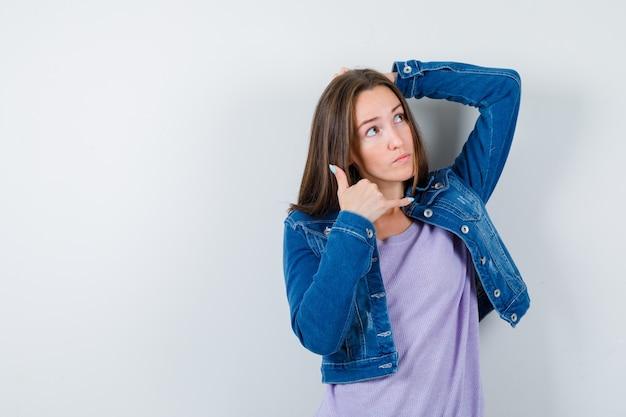 Giovane donna che mostra il gesto del telefono, alzando lo sguardo, tenendo la mano dietro la testa in maglietta, giacca e guardando pensierosa. vista frontale.