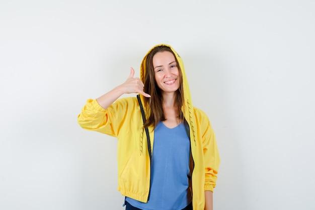Giovane signora che mostra il gesto del telefono in maglietta, giacca e sembra sicura. vista frontale.