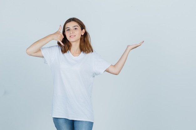 Young lady showing phone gesture while pretending to hold something in t-shirt, jeans and looking confident , front view.