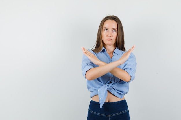 Young lady showing refusal gesture in blue shirt, pants and looking serious.