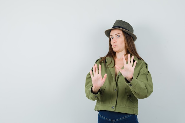 Молодая дама показывает жест отказа в шляпе пиджака и брюк и выглядит испуганной