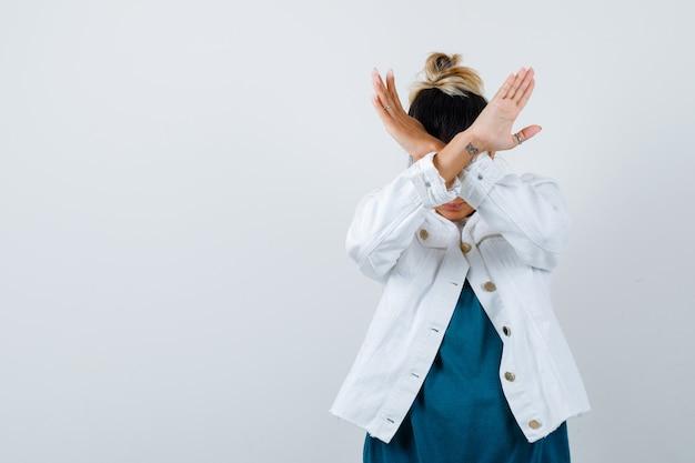 셔츠, 흰색 재킷에 거부 제스처를 보이고 자신감을 보이는 젊은 아가씨. 전면보기.