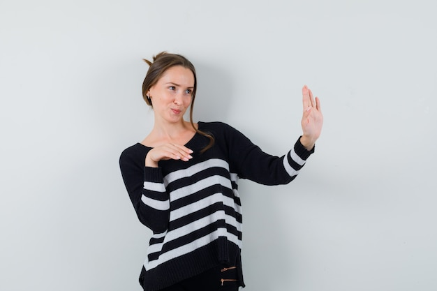 Young lady showing refusal gesture politely in shirt and looking cute