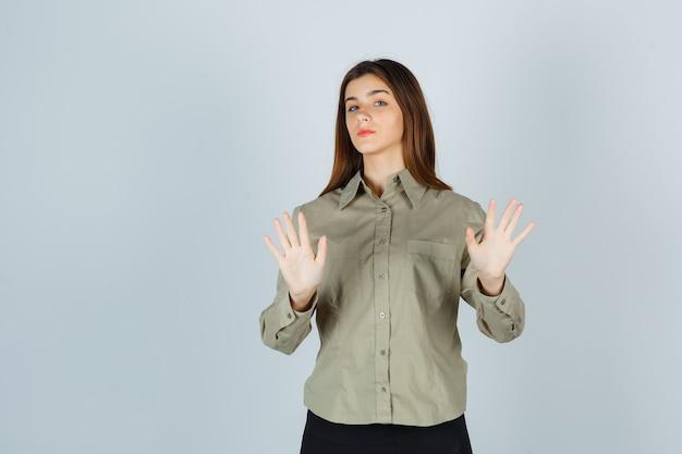 Giovane signora che mostra gesto di rifiuto in camicia, gonna e sembra seria. vista frontale.