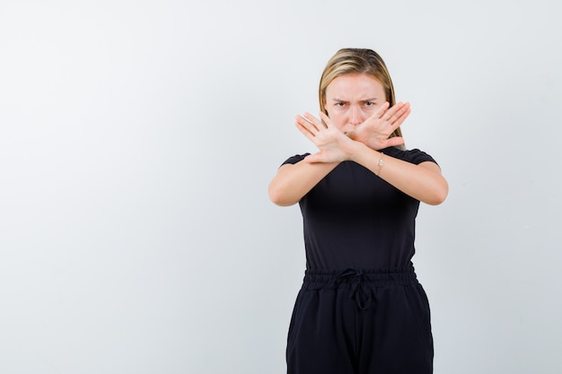 Young lady showing refusal gesture in t-shirt, pants and looking serious , front view.