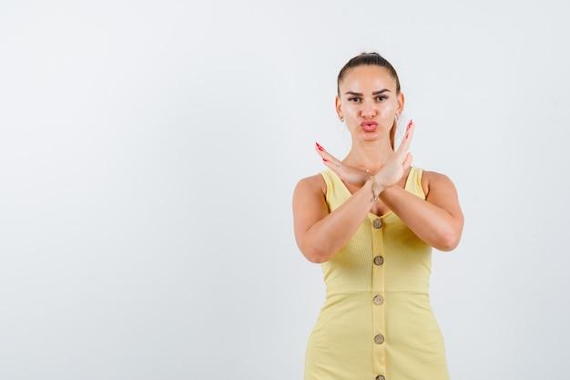 Giovane donna che mostra gesto di rifiuto in abito giallo e guardando fiducioso, vista frontale.
