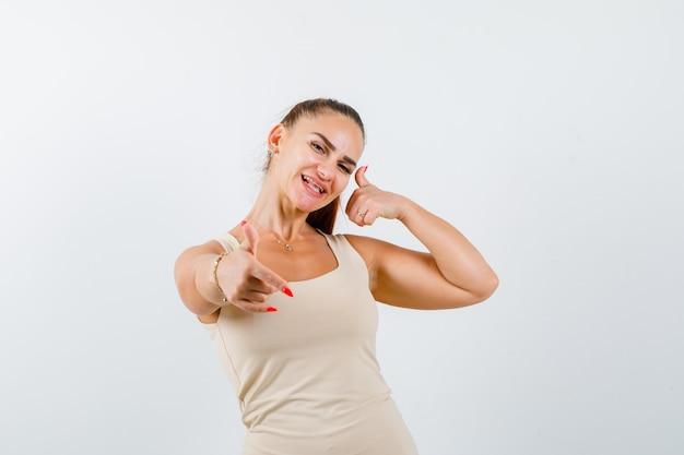 タンクトップでロックジェスチャーと親指を上に表示し、嬉しそうに見える若い女性、正面図。