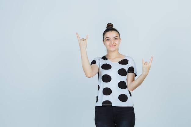 Tシャツ、ジーンズでロックジェスチャーを示し、クレイジーに見える若い女性、正面図。