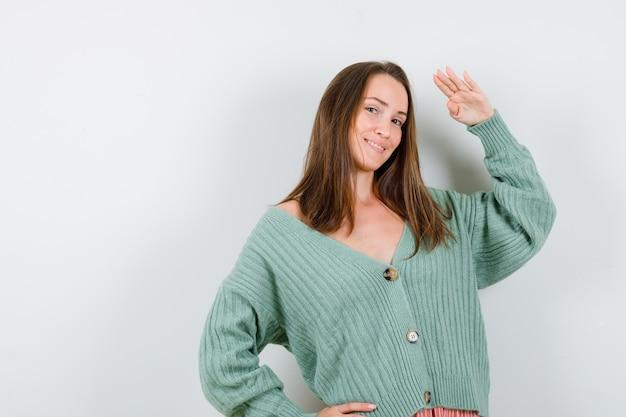 ウールのカーディガンで敬礼のジェスチャーを示し、陽気に見える若い女性、正面図。
