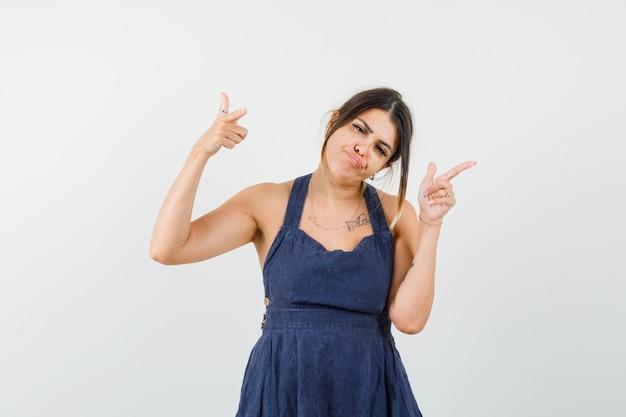 Молодая леди показывает жест стрельбы в платье и выглядит уверенно
