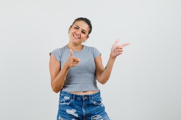 T- 셔츠, 반바지에 촬영 제스처를 보여주는 쾌활 한 찾고 젊은 아가씨.