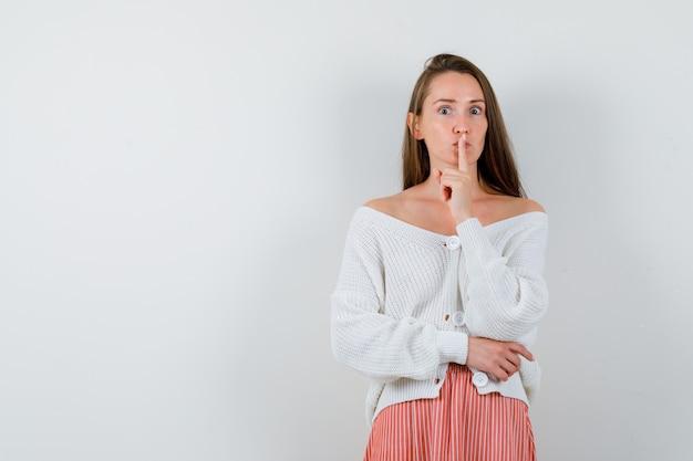 Giovane signora che mostra gesto di silenzio in cardigan e gonna che sembrano gravi isolati