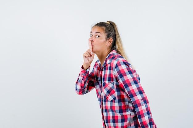 Giovane signora che mostra il gesto di silenzio in camicia a quadri e guardando attento, vista frontale.