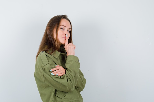 Giovane donna che mostra gesto di silenzio in giacca verde e sembra misteriosa, vista frontale.