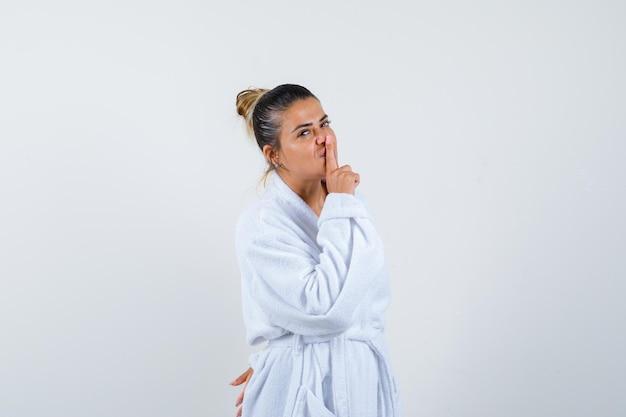 Молодая леди показывает жест молчания в халате и выглядит уверенно