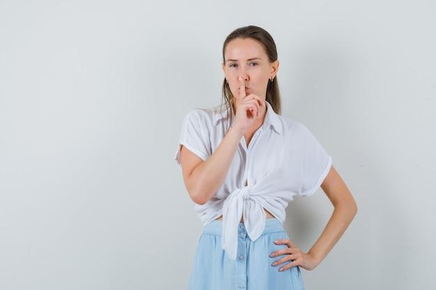 Молодая леди показывает жест молчания в блузке и юбке и смотрит осторожно