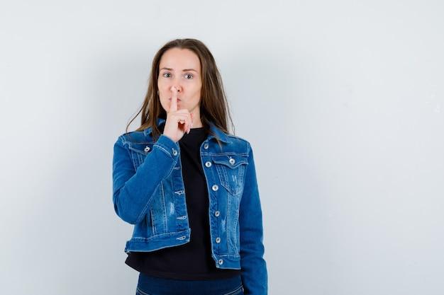 ブラウス、ジャケットで沈黙のジェスチャーを示し、自信を持って見える若い女性。正面図。