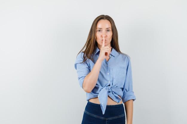 파란색 셔츠, 바지에 침묵 제스처를 보여주는 젊은 아가씨 조심스럽게 찾고