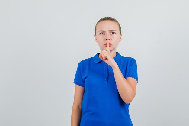 青いtシャツで沈黙のジェスチャーを示し、厳格に見える若い女性