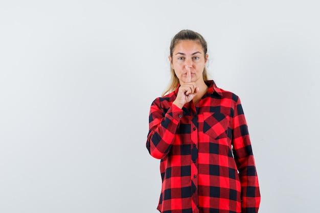 チェックシャツで沈黙のジェスチャーを示し、自信を持って見える若い女性