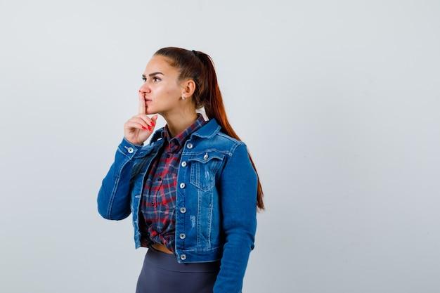 市松模様のシャツ、デニムジャケットで沈黙のジェスチャーを示し、注意深く見ている若い女性。正面図。