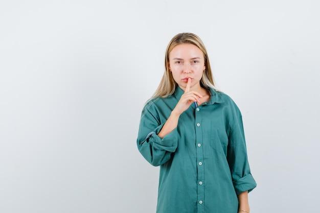緑のシャツで沈黙のジェスチャーを示し、賢明に見える若い女性。