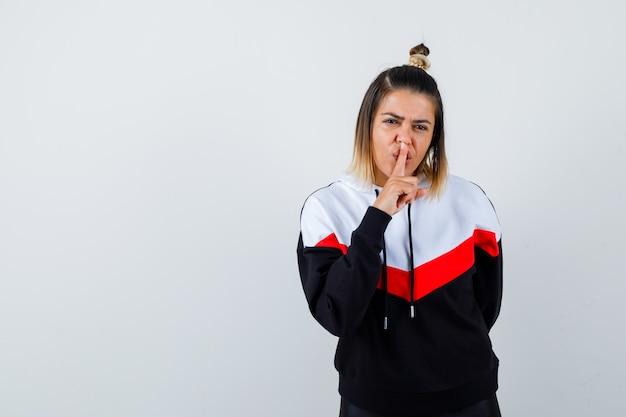 パーカーのセーターで沈黙のジェスチャーを示し、真剣に見える若い女性。