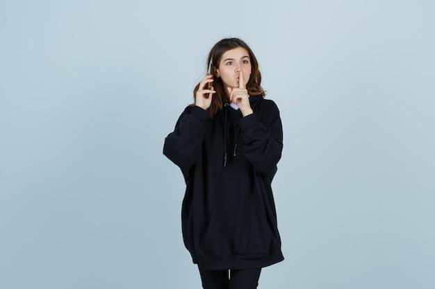 特大のパーカー、パンツで沈黙のジェスチャーを示し、真剣に見える若い女性。正面図。
