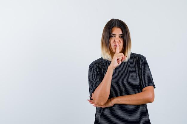 ポロドレスで沈黙のジェスチャーを示し、自信を持って、正面図を探している若い女性。