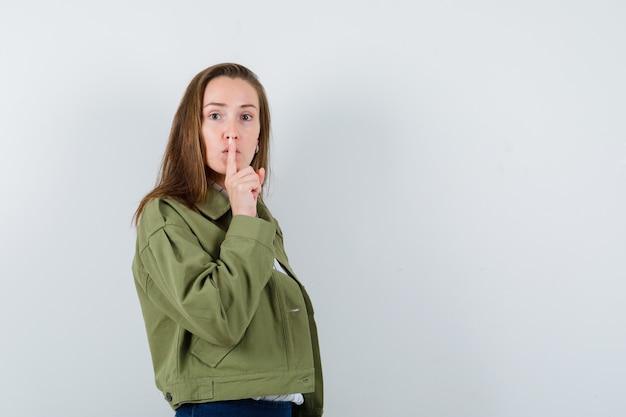 シャツ、ジャケットで沈黙のジェスチャーを示し、注意深く見ている若い女性、正面図。