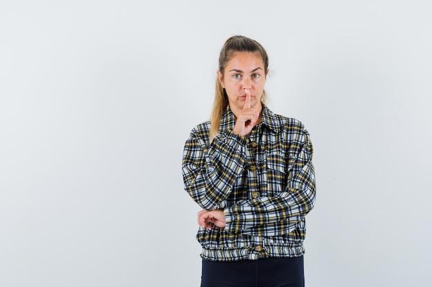 シャツ、ショートパンツで沈黙のジェスチャーを示し、自信を持って見える若い女性。正面図。 無料写真