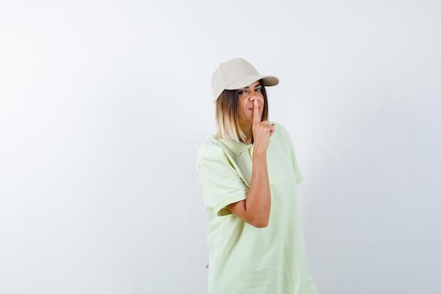 젊은 아가씨 t- 셔츠, 모자에 침묵 제스처를 보여주는 자신감, 전면보기를 찾고.