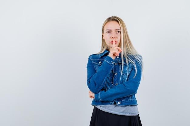 T- 셔츠, 데님 재킷, 치마에 침묵 제스처를 보여주는 젊은 아가씨 자신감을 찾고