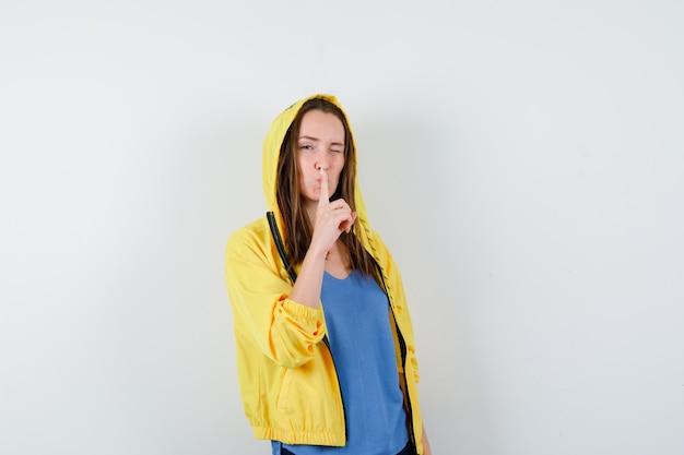 Tシャツ、ジャケット、自信を持って、正面図で沈黙のジェスチャーを示す若い女性。