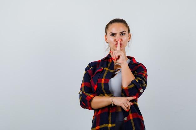 Молодая леди показывает жест молчания в верхней части, клетчатой рубашке и выглядит серьезным, вид спереди.