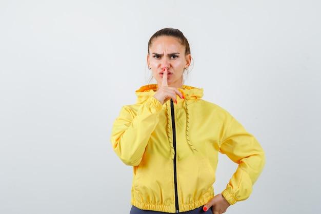 黄色いジャケットで沈黙のジェスチャーを示し、真剣に見える若い女性。正面図。