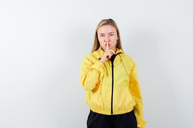 黄色のジャケット、ズボンで沈黙のジェスチャーを示し、注意深く見ている若い女性。正面図。