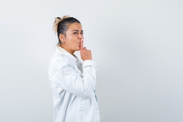 Young lady showing silence gesture in shirt, white jacket and looking careful. front view.