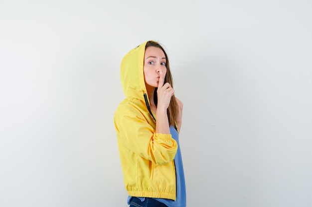 Young lady showing silence gesture in t-shirt, jacket and looking careful