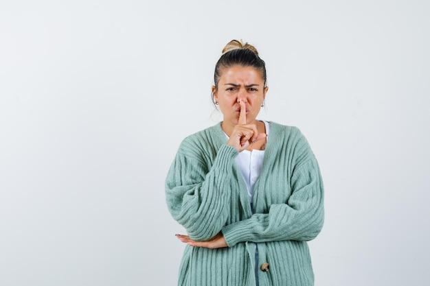 Giovane donna che mostra gesto di silenzio in maglietta, giacca e sembra sicura