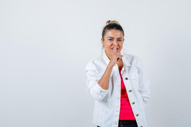 Giovane signora che mostra gesto di silenzio in maglietta, giacca bianca e sembra allegra. vista frontale.